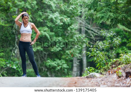 Athletic middle aged woman rests with her hands on her head and hips while on a run in green leaved woods on a dirt road in Surry, Maine, USA during the Summer. - stock photo