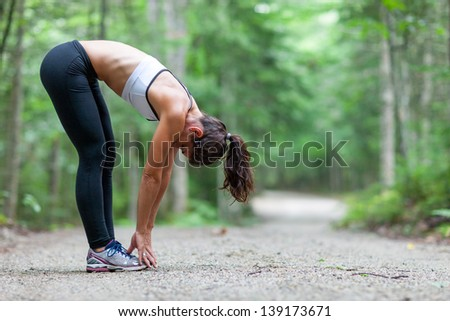 Athletic middle aged woman stretching in the green leaved woods on a dirt road before a run in Surry, Maine, USA during the Summer. - stock photo