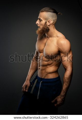 Athletic muscular bearded guy posing over grey background wall.