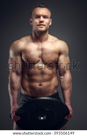 Athletic muscular man holds lifting weight. Isolated on a grey background. - stock photo