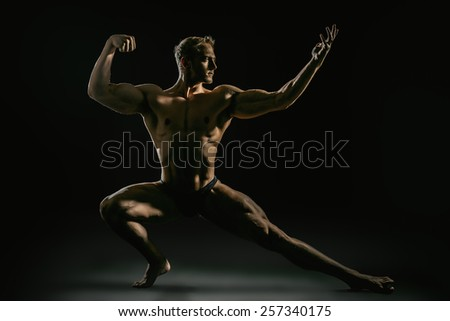 Athletic muscular man posing over black background. Men's beauty. Bodybuilding. Sports.  - stock photo
