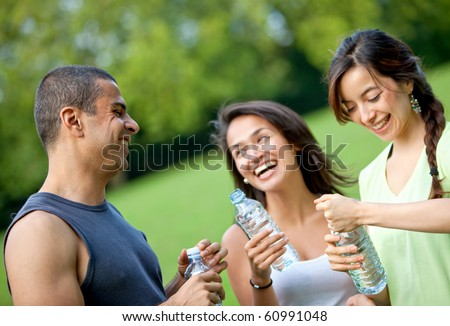 Athletic people holding bottles of water outdoors - stock photo