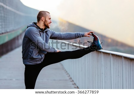 Athletic runner doing stretching exercise, preparing for morning workout in the park - stock photo