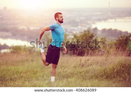 Athletic runner doing stretching exercise, preparing for running in the nature with the city in background. Healthy lifestyle - stock photo