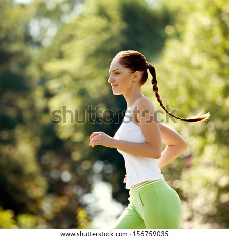 Athletic Runner Training in a park for Marathon. Fitness Girl Running outdoors - stock photo