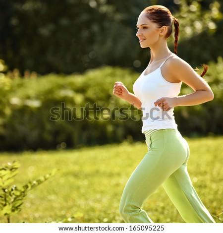 Athletic Runner Training in a park for Marathon. Fitness Girl Running outdoors - stock photo