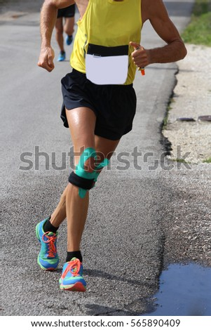 athletic runner with elastic band at the knee running fast during the sporting event on the road