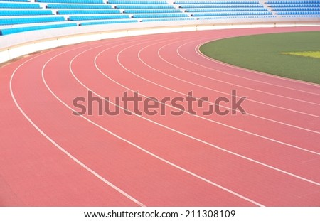 athletic running track lanes with rows of stadium seats in background - stock photo