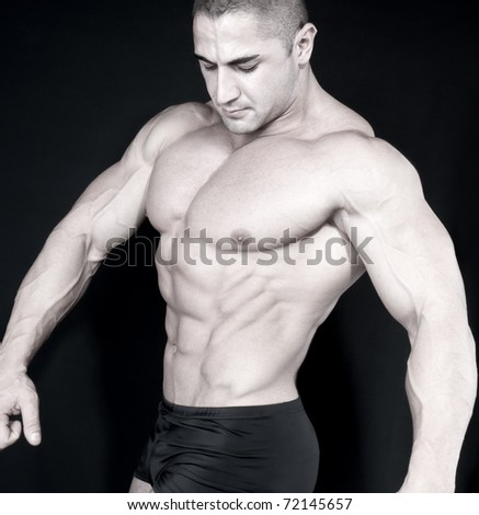 Athletic sexy attractive male body builder, demonstrating contest pose. Studio shot - stock photo