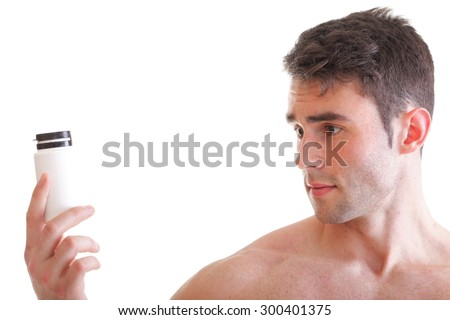 Athletic sexy male body builder holding a box with supplements, man holding bottle of pills - stock photo