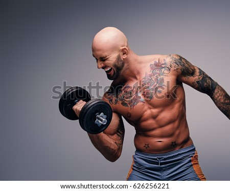 Athletic shaved head male with tattoos on his torso and arms holds dumbbell isolated on grey vignette background.