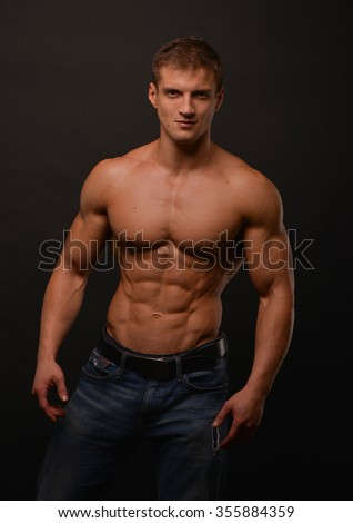 athletic shirtless male model flexing muscles