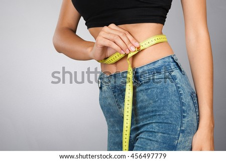 Athletic slim woman measuring her waist by measure tape  - stock photo