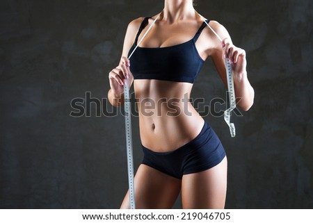 Athletic slim woman with measure tape after diet over dark gray background