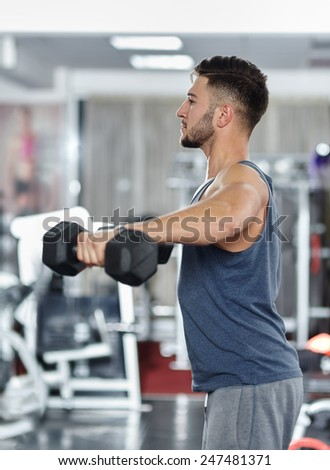 Athletic slim young man working out with dumbbells in a gym - stock photo