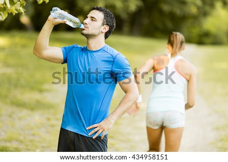 Athletic sport man drinking water from a bottle - stock photo