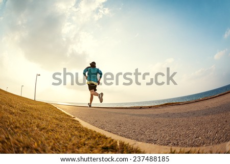 athletic sportsman running in the park near the ocean in the sunset - stock photo