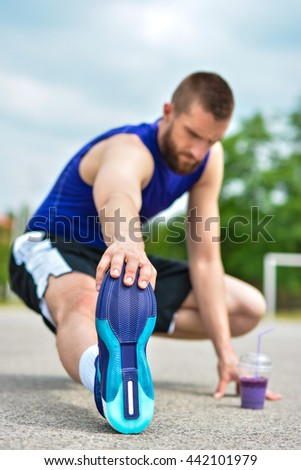 Athletic sportsman with a bottle of detox smoothie sitting and doing warming stretching exercise in the park - stock photo