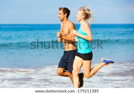 Athletic sporty couple jogging together on the beach - stock photo