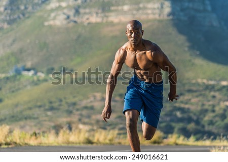 Athletic, sporty, muscular, healthy black male running along a road outdoors with a mountain background.  - stock photo