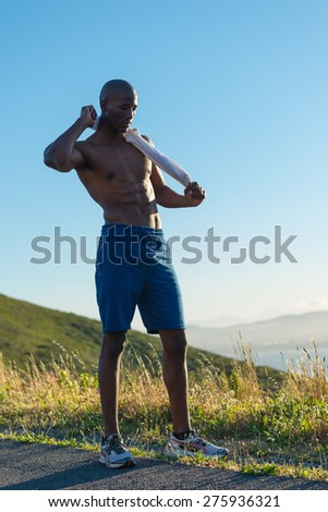 Athletic, sporty, muscular, healthy black male undressing by taking his white vest off, along a road outdoors with a mountain background while resting - stock photo