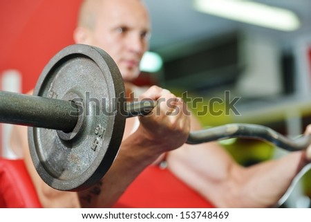 Athletic strong bodybuilder, execute exercise training in sport gym hall - stock photo