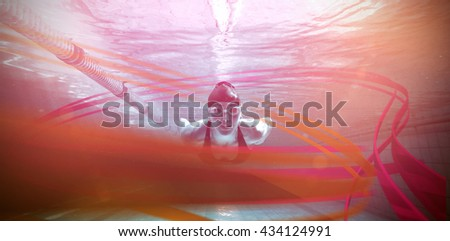 Athletic swimmer training on her own against feet of woman standing on the edge of the pool - stock photo