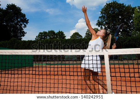 Athletic tennis player hitting a ball over the net on the court - stock photo