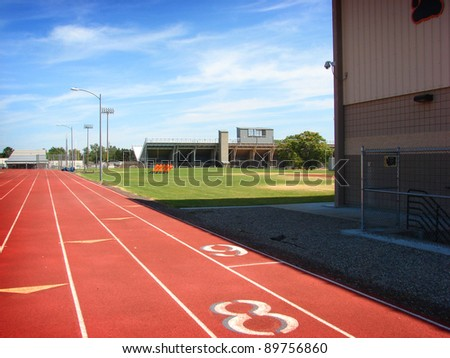 athletic track with sports stadium in background - stock photo