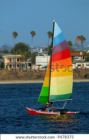 Athletic woman adjusts rigging on her yacht in Mission Bay, San Diego, California with a parasail in the background. - stock photo