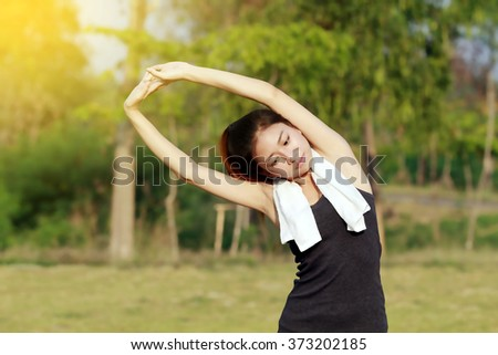 Athletic woman asia warming up and Young female athlete sitting on an exercising and stretching in a park before Runner outdoors, healthy lifestyle concept - stock photo
