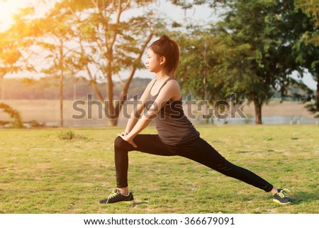 Athletic woman asian warming up and Young female athlete sitting on an exercising and stretching in a park before Runner outdoors, healthy lifestyle concept  - stock photo