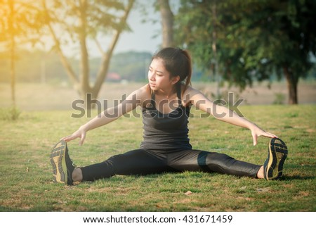 Athletic woman asian warming up and Young female athlete sitting on an exercising and stretching in a park before Runner outdoors, healthy lifestyle concept,blurry and soft focus - stock photo