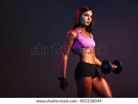 athletic woman. athletic girl with dumbbells. Studio photography. smoke effects. healthy athletic girl with massive dumbbells in his hands. working muscles. sport.dry working muscles. - stock photo