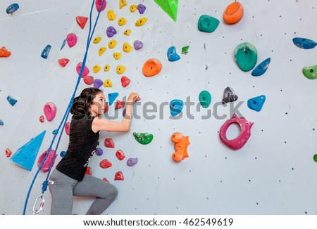 Athletic woman climbing indoors, view from the back