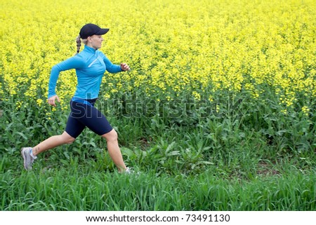 Athletic woman cross country running on spring. Healthy lifestyle concept. - stock photo
