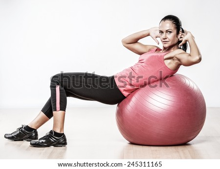 Athletic woman doing exercise on a fitness ball - stock photo