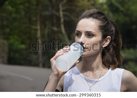 Athletic woman drinking water, while training outdoors in a natural setting. Action and healthy lifestyle concept. - stock photo