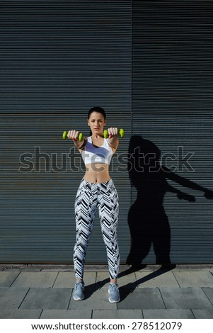 Athletic woman holding weights with hands up at her front getting arms in great shape, female with beautiful figure working out lifting dumbbells against black copy space background for text message - stock photo