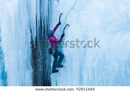 athletic woman in pink coat climbing ice in Ouray, Colorado - stock photo