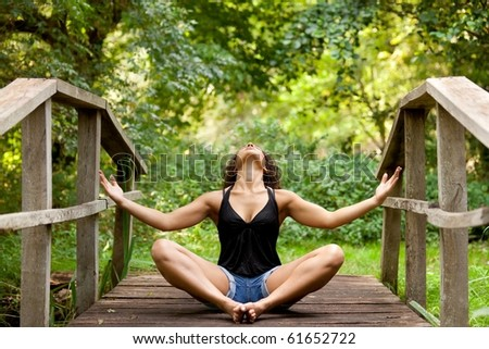 athletic woman in short jean practicing relaxation in nature