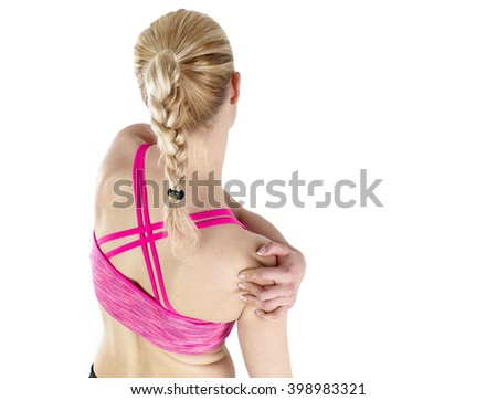 Athletic woman in sports wear pressing her hand against a painful shoulder - stock photo