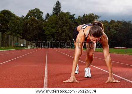 Athletic woman in start position on track - stock photo