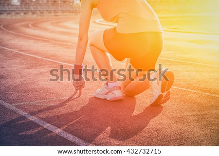 Athletic woman in start position on track  , sunset , vintage tone - stock photo
