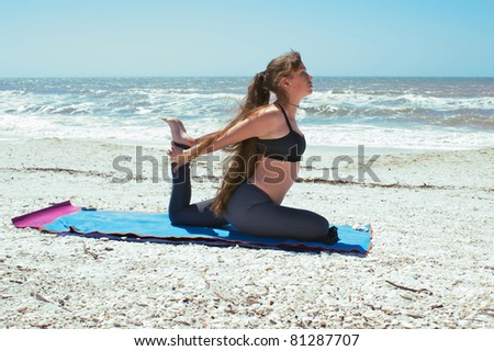 athletic woman is doing yoga exercise on beach in Kapotasana or Pigeon Pose both arms back holding foot on an empty beach at the gulf of mexico in bonita springs florida with long hair blowing in wind - stock photo