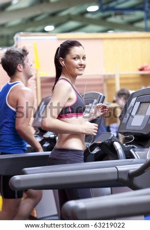 Athletic woman listening to the music while using a treadmill in a sport centre with her boyfriend - stock photo