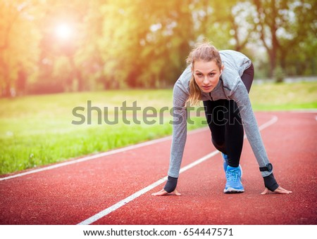 Athletic Woman On Running Track Getting Ready To Start Run