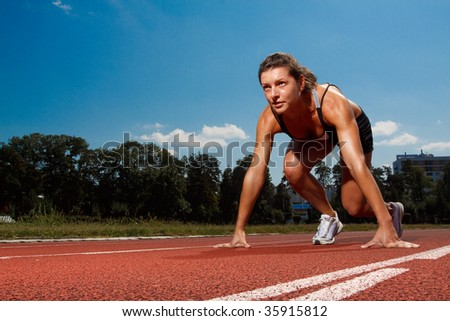 Athletic woman on track starting to run - stock photo