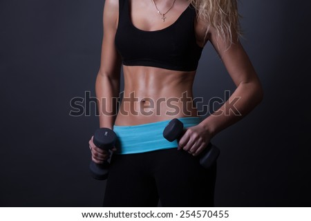 Athletic woman pumping up muscles with dumbbells.