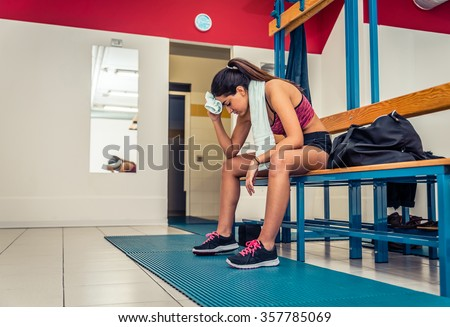 Athletic woman relaxing in a gym locker room after an intensive workout - Tired sportive girl in a fitness center - stock photo
